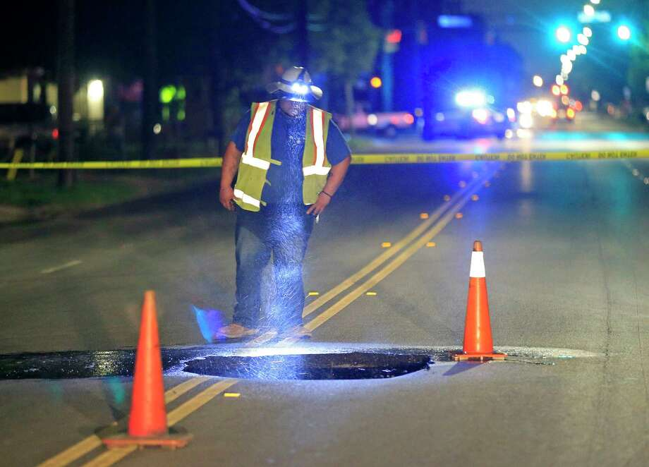 A San Antonio Water System employee looks at a hole caused by a water main break in the middle of the 700 block of Divison Ave. near IH-35 south Thursday Aug. 17, 2017. Divison Ave. between Bruhn St. and Commercial Ave. was closed, for SAWS to make a repair. Photo: Edward A. Ornelas, San Antonio Express-News / © 2017 San Antonio Express-News