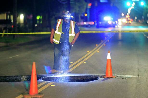 A San Antonio Water System employee looks at a hole caused by a water main break in the middle of the 700 block of Divison Ave. near IH-35 south Thursday Aug. 17, 2017. Divison Ave. between Bruhn St. and Commercial Ave. was closed, for SAWS to make a repair.