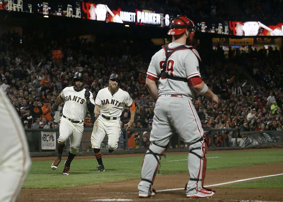 San Francisco Giants' Denard Span, left, and Hunter Pence run toward home to score as Philadelphia Phillies catcher Cameron Rupp waits for the throw, in San Francisco onAug. 17, 2017. Photo: Jeff Chiu, Associated Press