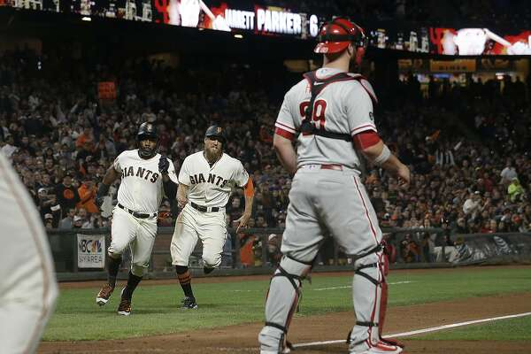 San Francisco Giants' Denard Span, left, and Hunter Pence, second from left, run toward home to score as Philadelphia Phillies catcher Cameron Rupp, right, waits for the throw during the fifth inning of a baseball game in San Francisco, Thursday, Aug. 17, 2017. (AP Photo/Jeff Chiu)