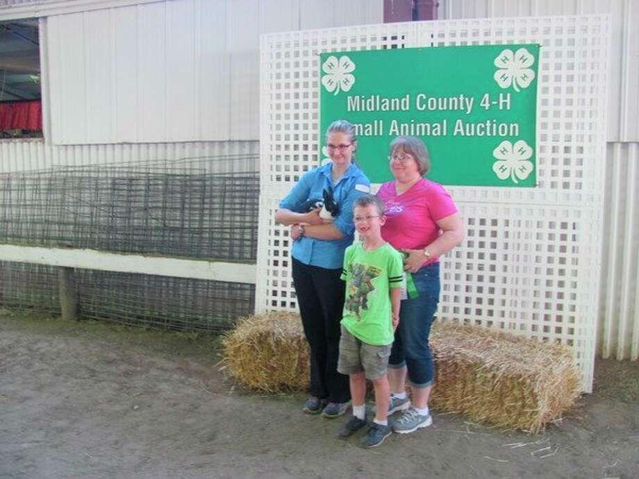 Lehman Award winner Anna Martin, left, with members of the Rudy Rezler family, who purchased Martin's Havana Sr. Buck rabbit at Wednesday's Midland County 4-H Small Animal Auction. (John Kennett/jkennett@mdn.net)