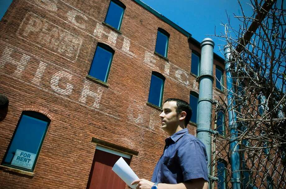 Jonathan Reiss, who's blog is called Streets of Stamford, has found buildings with old painted signs throughout the city. He stands in front of a building on Pacific Street in Stamford, Conn. on Friday June 18, 2010. Photo: Kathleen O'Rourke / Stamford Advocate