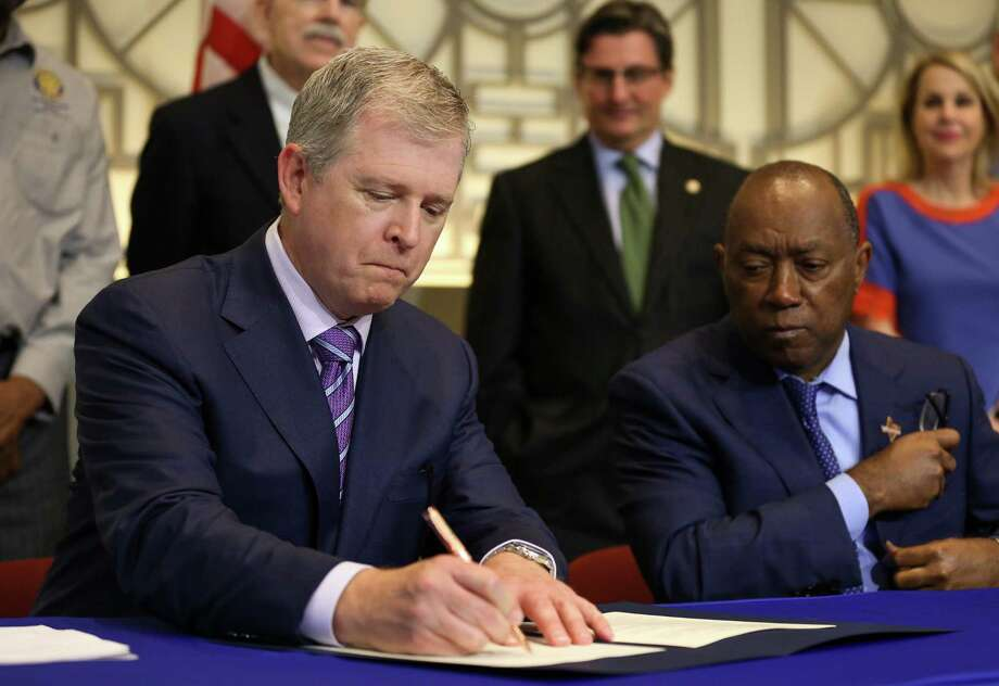 Texas Central Partners president Tim Keith, left, follows Houston Mayor Sylvester Turner in signing the memorandum of understanding for support of construction of a high-speed rail system that would connect the city with Dallas on Aug. 17. Photo: Godofredo A. Vasquez / Houston Chronicle
