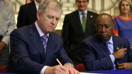 "Central Texas President Tim Keith, left, follows Houston Mayor Sylvester Turner in signing the ""memorandum of understanding"" for support of construction of a high-speed rail system that would connect the city with Dallas Thursday, Aug. 17, 2017, in Houston."