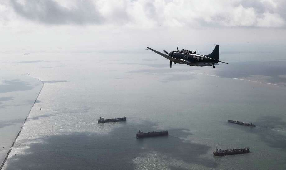 A Douglas SBD Dauntless flies over Galveston Bay, as aircraft from the Lone Star Flight Museum are relocated from their previous home on Galveston Island to the new museum at Ellington Field, Tuesday, August 15, 2017, in Galveston. Photo: Jon Shapley / Houston Chronicle
