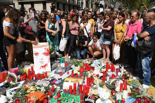TOPSHOT - People stand next to flowers, candles and other items set up on the Las Ramblas boulevard in Barcelona as they pay tribute to the victims of the Barcelona attack, a day after a van ploughed into the crowd, killing 13 persons and injuring over 100 on August 18, 2017.  Police hunted for the driver who rammed a van into pedestrians on an avenue crowded with tourists in Barcelona, leaving 13 people dead and  more than 100 injured, just hours before a second assault in a resort along the coast. / AFP PHOTO / PASCAL GUYOTPASCAL GUYOT/AFP/Getty Images
