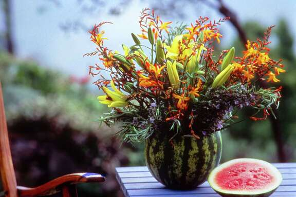 Create a vase from a watermelon and fill with Asiatic lilies and crocosmia.