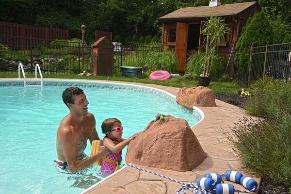 Thomas Kearney teaches Charlotte Smith, 3, how to swim at her home on Tuesday, Aug. 15, 2017 in Clifton Park, N.Y. (Lori Van Buren / Times Union)