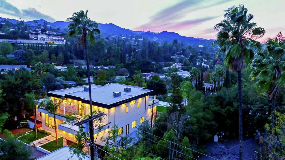 Los Angeles Chargers tight end Antonio Gates bought a newly built compound on a hilltop in the city's Encino neighborhood for $6.995 million. The contemporary showplace is amped up with amenities such as a floor-to-ceiling fireplace, a glass-enclosed wine cellar and a cook's kitchen. Rectractable walls of glass lead to an 800-square-foot covered patio with a fireplace and cooking center. (Rani Sikolsky/TNS) Photo: Rani Sikolsky / Los Angeles Times
