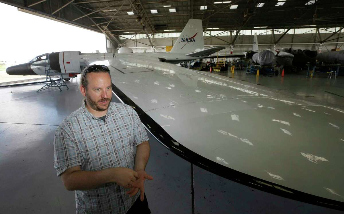 Amir Caspi, Southwest Research Institute senior research scientist, talks about the NASA WB-57F jet that will used for research during the eclipse shown at Ellington Airport Thursday, Aug. 10, 2017, in Houston. The long wings of the jet allows for extreme high altitude flight. Two WB-57F jets will be flown from Ellington Airport to observe Mercury and the sun at 50,000 feet during the eclipse using telescopes with cameras. ( Melissa Phillip / Houston Chronicle )
