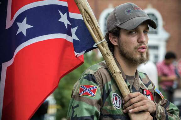 Ben, a 21-year-old KKK member from Harrison, Arkansas, attends the rally at Emancipation Park. This week, internet sleuths are combing through thousands of photos taken at the white supremacist rally in Charlottesville, Va., over the weekend. Anti-racism activists aim to name and shame the participants and get them fired. Companies have little choice when they discover an employee is proclaiming white supremacy or white nationalism.