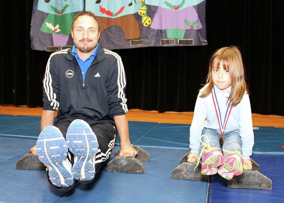 Former Olympian and gymnastics world champion Sean Townsend and Silverlake Elementary student Vera Thompson demonstrate the L-sit gymnastics exercise. Townsend gave a motivational grit speech at Silverlake Dec. 15, encouraging students to set goals and reminders for themselves and to be tough despite challenges. Although he started at age 10 -- later than most other gymnasts -- Townsend went on to compete in the 2000 Olympic Games in Sydney and won the world championship in parallel bars in 2001. He currently co-owns Pearland Gymnastics Academy. / Internal