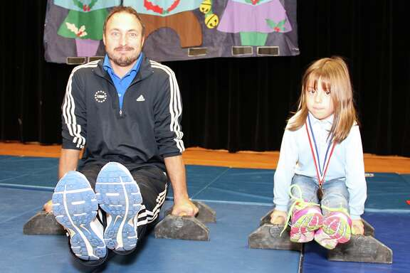 Former Olympian and gymnastics world champion Sean Townsend and Silverlake Elementary student Vera Thompson demonstrate the L-sit gymnastics exercise. Townsend gave a motivational grit speech at Silverlake Dec. 15, encouraging students to set goals and reminders for themselves and to be tough despite challenges. Although he started at age 10 -- later than most other gymnasts -- Townsend went on to compete in the 2000 Olympic Games in Sydney and won the world championship in parallel bars in 2001. He currently co-owns Pearland Gymnastics Academy.