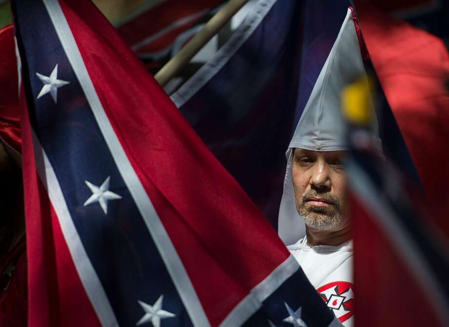 (FILES) This file photo taken on July 08, 2017 shows a member of the Ku Klux Klan during a rally, calling for the protection of Southern Confederate monuments, in Charlottesville, Virginia. A sizeable contingent of members of the extreme right and white nationalists are expected to descend on a small US university town on August 12, 2017 -- and a fierce opposition front is uniting against it.Thousands of white nationalists, including supporters of the Ku Klux Klan white supremacist group, and anti-fascist activists are expected to clash in Charlottesville, Virginia, a sleepy town planning to remove a statue of General Robert E. Lee, who led Confederate forces in the US Civil War.  / AFP PHOTO / ANDREW CABALLERO-REYNOLDSANDREW CABALLERO-REYNOLDS/AFP/Getty Images Photo: ANDREW CABALLERO-REYNOLDS, AFP/Getty Images