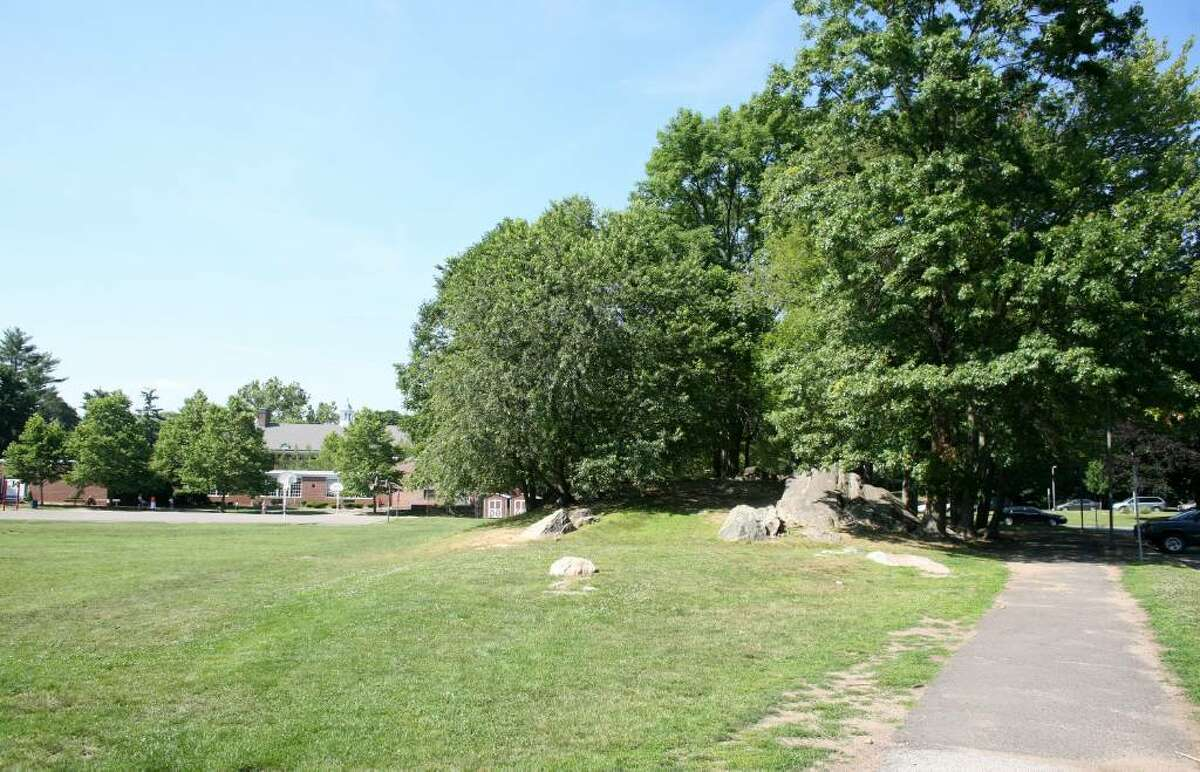 Some North Mianus School parents object to the expansion of the parking area in front of the school that would eliminate the trees and rock outcropping shown at right.