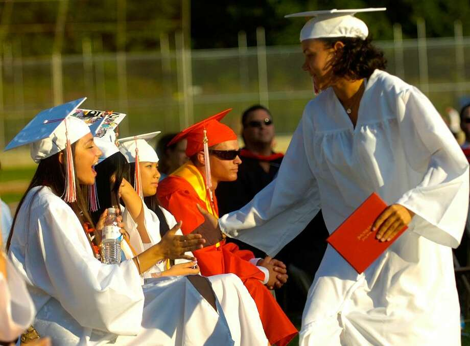 Desantilia Gjata gives a congratulatory high-five to Sasha Hamlin after they both received their diplomas during the Derby High School graduation ceremony Friday, June 18, 2010. Photo: Lindsay Niegelberg / Connecticut Post