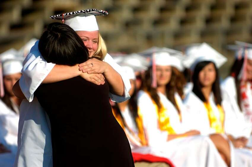 Samantha Tabone gets a hug after being awarded a scholarship during the Derby High School graduation ceremony Friday, June 18, 2010.