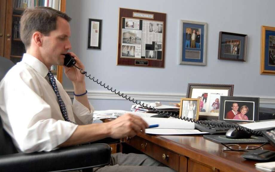 U.S. Rep. Jim Himes, D-Conn., in his Washington, D.C., office this past week. Family photos, from left, a wedding photo, photos of his two daughters and a photo of Himes and his wife Mary, are shown on his desk. Meredith McDermott/Contributed photo Photo: Contributed Photo / Greenwich Time Contributed