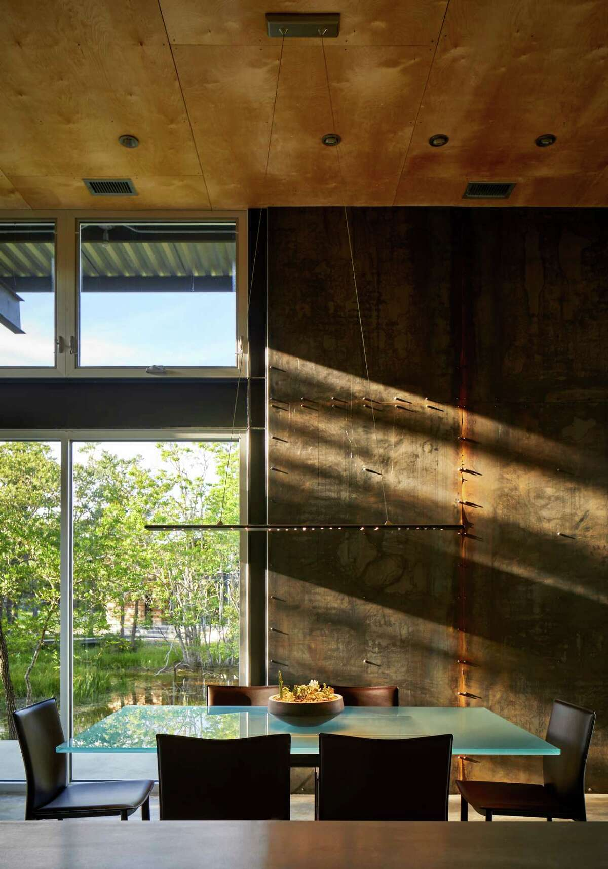 The dining room table is made of glass and Corten steel then surrounded by contemporary brown leather chairs.
