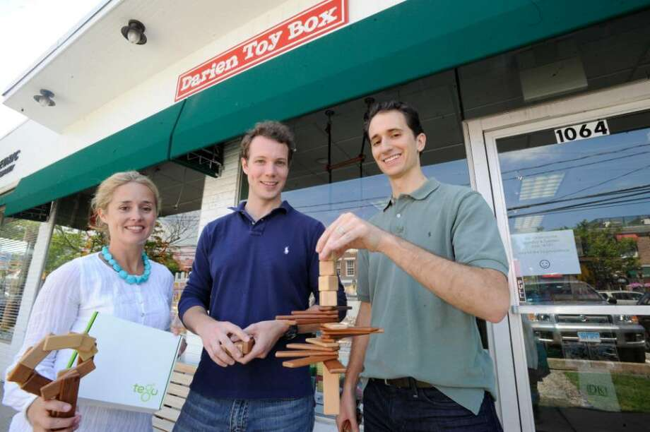 Founders of Tegu, from left: Kate Motley, Will Haughey, of Rowayton, and Brandon Straub, of New York City, hold up their product, as they stand in front of the Darien Toy Box, which will soon carry the product, on Tuesday, June 15, 2010. Photo: Helen Neafsey / Greenwich Time