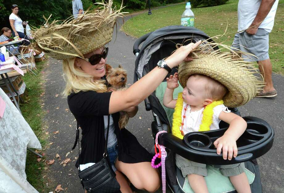 Jen Matsen from Norwalk trys to get a just bought straw hat on her 14-month-old daughter Courtney while holding her dog Kit Kat as they shop for unique items at the Lockwood-Mathews Mansion Museum Old-Fashioned Flea Market and antique car show in Norwalk. Photo: Alex Von Kleydorff / Hearst Connecticut Media File / Connecticut Post