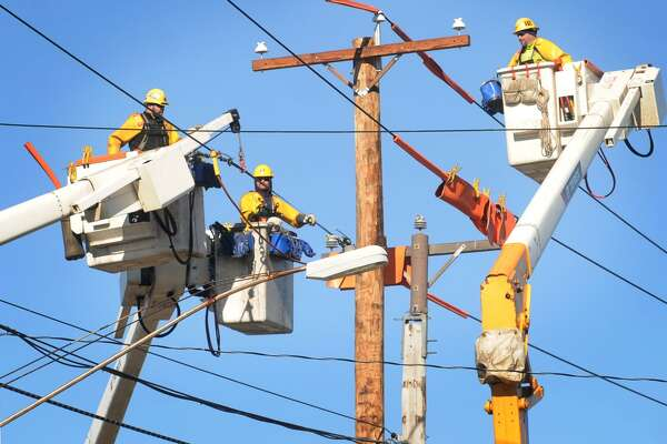 A United Illuminating crew work together out of three separate bucket lifts to install powerlines on new utility poles along Main Street in Stratford, Conn. on Tuesday, February 2, 2016. The work is part of scheduled equipment upgrades.