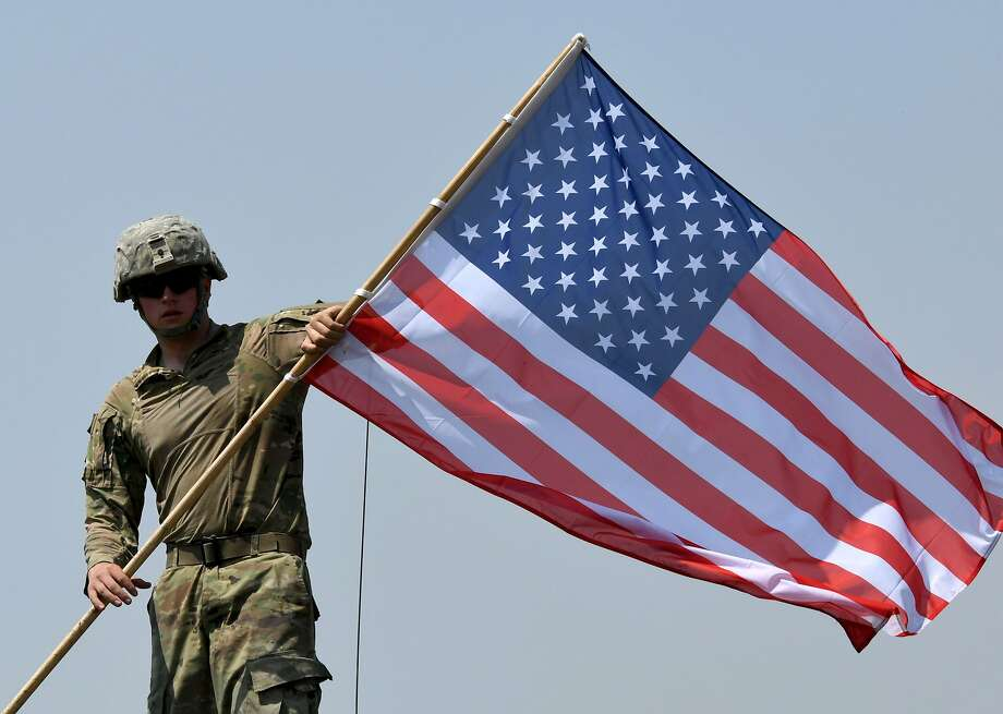 """An American soldier carries a U.S. flag during the closing ceremony of the multinational military exercise """"Noble Partner 2017"""" at the military base of Vaziani, outside Tbilisi, Georgia, on Aug. 12. Photo: VANO SHLAMOV, AFP/Getty Images"""