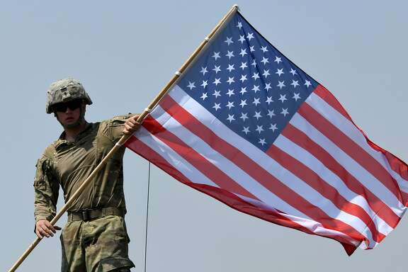 An American soldier carries a US flag during the official closing ceremony of the multinational military exercise 'Noble Partner 2017' at the military base of Vaziani, outside Tbilisi, Georgia, on August 12, 2017.  The Noble Partner 2017 is large scale exercise with engagement of NATO members and partner countries: Georgia, USA, UK, Germany, Turkey, Slovenia, Armenia and Ukraine. / AFP PHOTO / Vano ShlamovVANO SHLAMOV/AFP/Getty Images