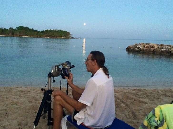 Bill Kramer adjusts his telescope to view a lunar eclipse in Jamaica in 2015.