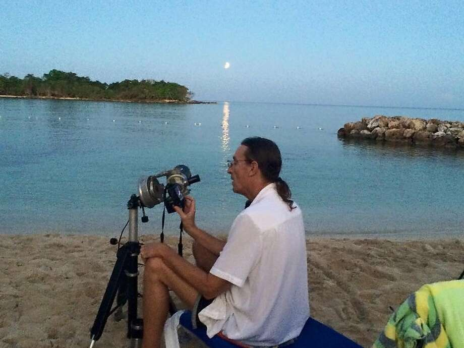 Eclipse aficionado Bill Kramer adjusts his telescope for the 2015 lunar eclipse in Jamaica.
