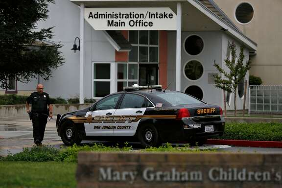 A San Joaquin County Sheriff's deputy walks back to his car after responding to a call to Mary Graham Children's Shelter April 6, 2017 in French Camp, Calif.