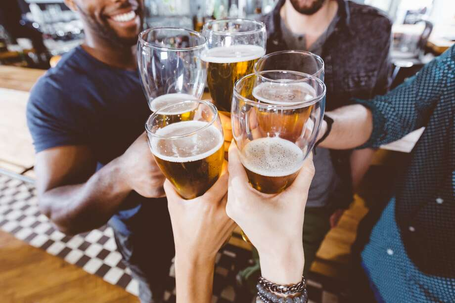 A group of friends drink beer at a pub. Photo: Izusek / Getty Images