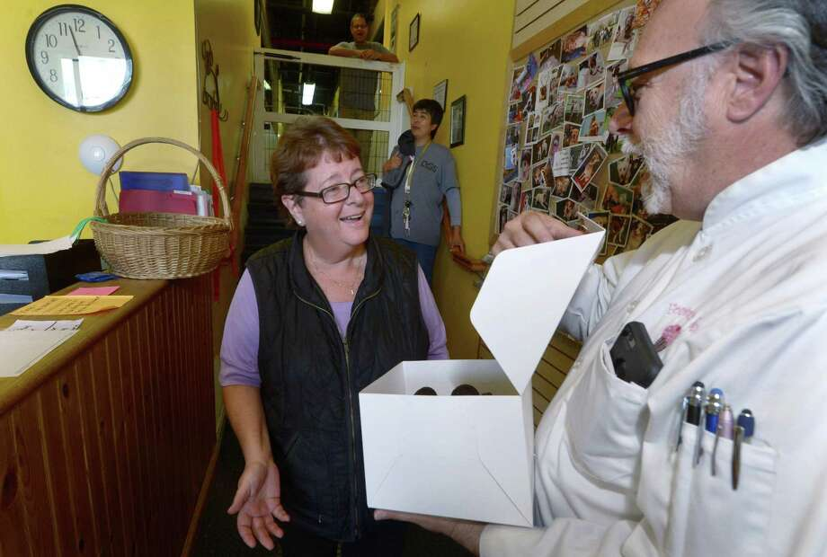 Sky Mercede, right, delivers a free cake in early August 2017 to Debbie Modica, general manager of Dog Gone Smart in Norwalk, whom an acquaintance had nominated to receive one for free. Throughout August, Mercede's Forever Sweet Baker in Norwalk has delivered a cake a day to people nominated by others to receive one as an act of kindness. Photo: Erik Trautmann / Hearst Connecticut Media / Norwalk Hour