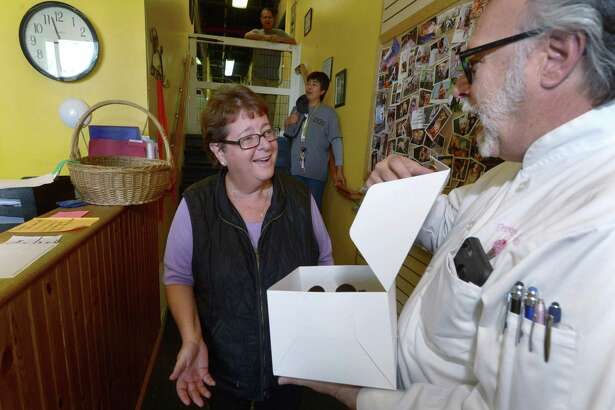 Sky Mercede, right, delivers a free cake in early August 2017 to Debbie Modica, general manager of Dog Gone Smart in Norwalk, whom an acquaintance had nominated to receive one for free. Throughout August, Mercede's Forever Sweet Baker in Norwalk has delivered a cake a day to people nominated by others to receive one as an act of kindness.