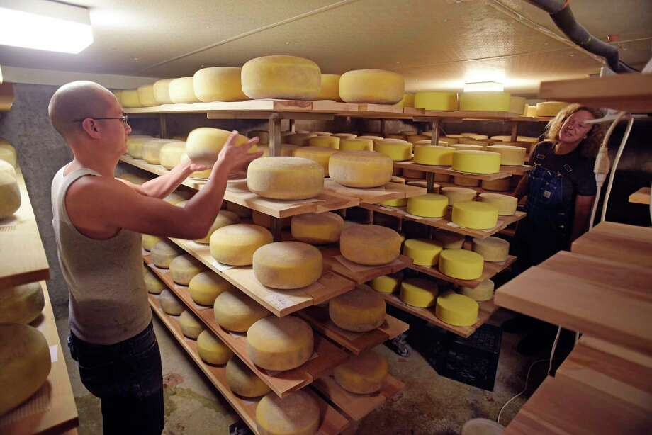 Vi Wood, left, and farmer Beatrice Berle, background right, work in the cheese cellar flipping the cheeses at the Berle Farm on Wednesday, July 26, 2017, in Hoosick, N.Y.    (Paul Buckowski / Times Union) Photo: PAUL BUCKOWSKI / 20041133A