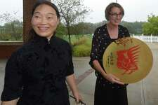 Zibo #1 High School teacher Lu Hui presents a gift to Center for Global Studies director Julie Parham as thirteen exchange students and two teachers from China arrive for a five-day visit at Brien McMahon High School Friday, August 18, 2017, in Norwalk, Conn.