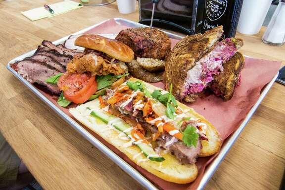 Brotherton's Black Iron Barbecue in Pflugerville serves brisket, clockwise from top left; turkey; pork chop; boudin; a Texas reuben sandwich; brisket banh mi sandwich; and fried chicken sandwich.