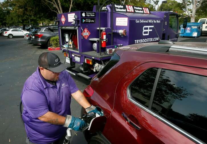 Cesar Guzman fills the gas tank of a car parked in the Technology Credit Union parking lot from his Booster mobile refueling truck in San Jose, Calif. on Friday, Aug. 11, 2017.