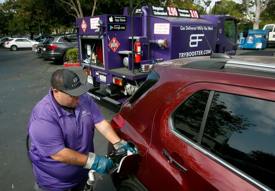 Cesar Guzman, a Booster mobile refueler, fills the gas tank of a car in the Technology Credit Union parking lot. Photo: Paul Chinn, The Chronicle