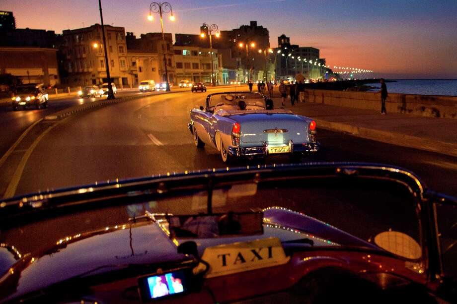 Convertible taxis drive along El Malecon in Havana. Tip: Pay extra for the yellow cabs, which have seatbelts for every passenger, front and rear. Photo: Michael Ciaglo / Michael Ciaglo