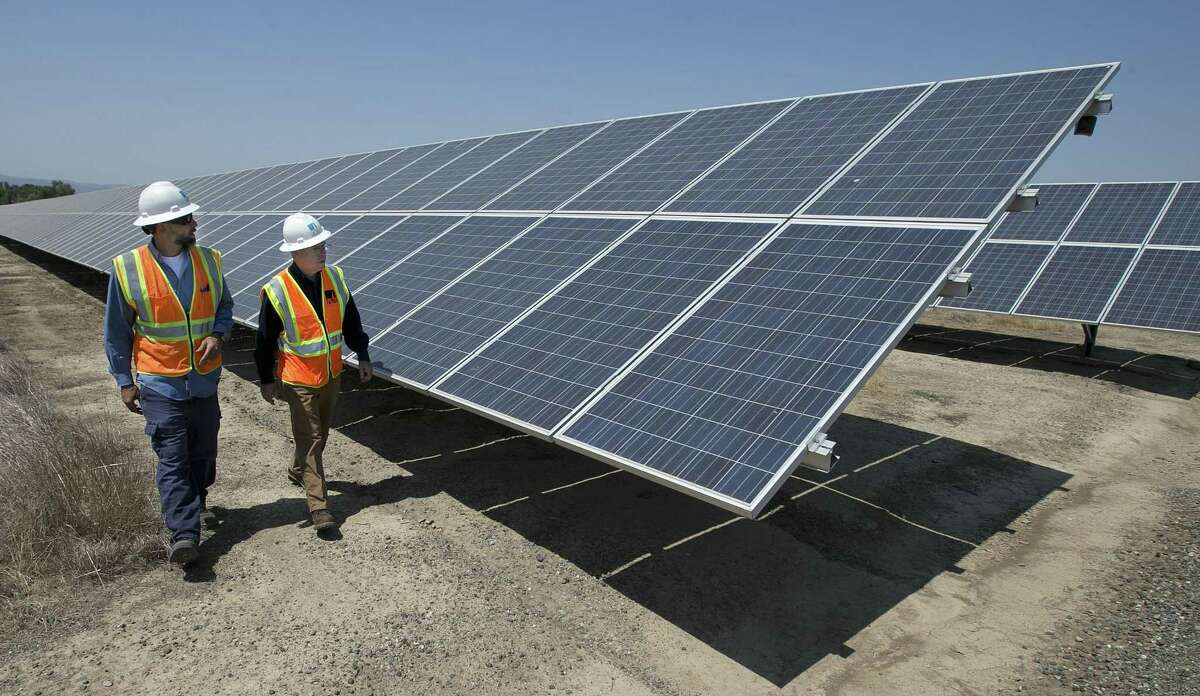 Solar Tech Joshua Valdez, left, and Senior Plant ManagerTim Wisdom walk past solar panels.