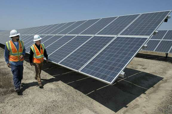 Solar Tech Joshua Valdez, left, and Senior Plant ManagerTim Wisdom walk past solar panels and at a Pacific Gas and Electric Solar Plant, Thursday, Aug. 17, 2017, in Vacaville, Calif. Power grid managers say they've been preparing extensively for more than a year for this Monday's solar eclipse and that by ramping up other sources of power, mainly hydroelectric and natural gas, they are confident nobody will lose power or see a spike in energy prices. (AP Photo/Rich Pedroncelli)