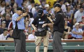 Umpires check a video replay during the sixth inning of a baseball game in Boston, Monday, Aug. 14, 2017. (AP Photo/Charles Krupa)
