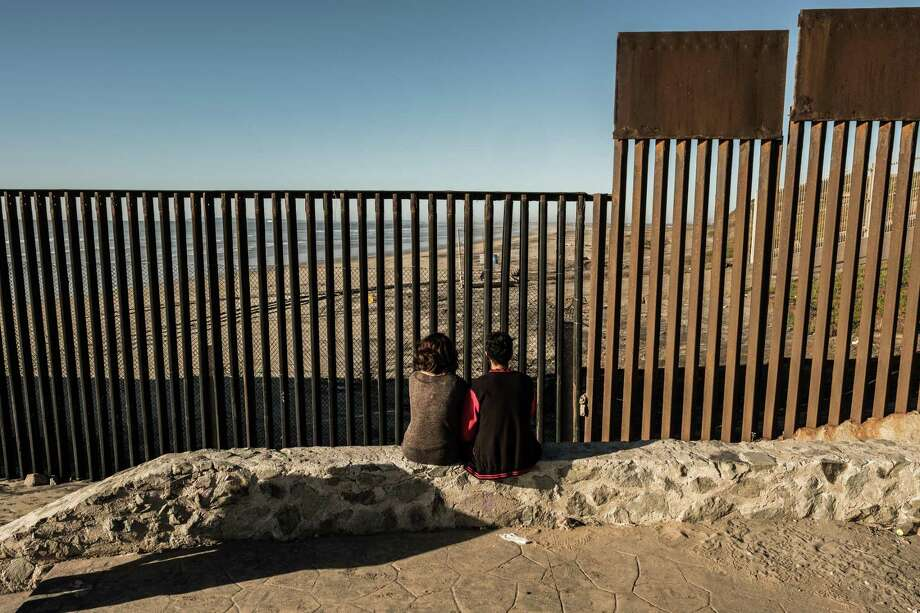 A couple sits by a border fence in Tijuana between the the United States and Mexico. A reader says a real wall is better than the virtual wall being discussed by some members of Congress. Photo: BRYAN DENTON /NYT / NYTNS