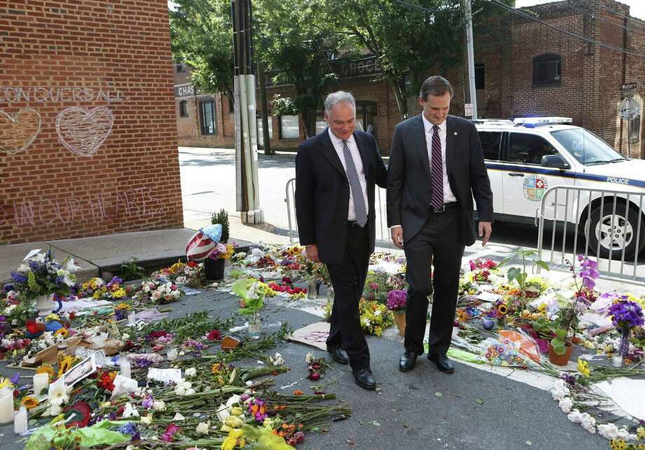 "Sen. Tim Kaine, left, and Charlottesville mayor Michael Signer visit a makeshift memorial Wednesday. Signer was quick to lay blame for the unrest in his city ""at the doorstep of the White House and the people around the president."" Photo: Julia Rendleman /Associated Press / Julia Rendleman"