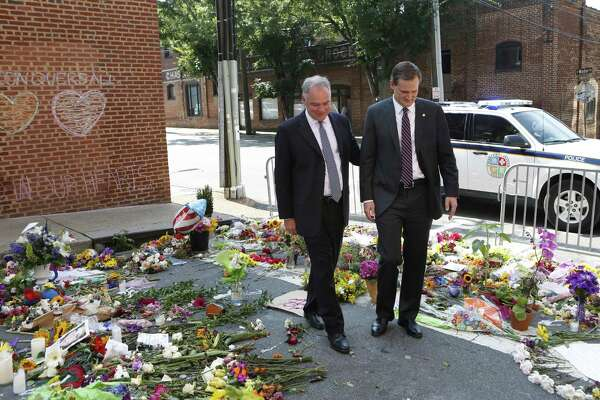 """Sen. Tim Kaine, left, and Charlottesville mayor Michael Signer visit a makeshift memorial Wednesday. Signer was quick to lay blame for the unrest in his city """"at the doorstep of the White House and the people around the president."""""""