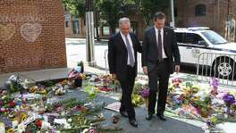 "Sen. Tim Kaine, left, and Charlottesville mayor Michael Signer visit a makeshift memorial Wednesday. Signer was quick to lay blame for the unrest in his city ""at the doorstep of the White House and the people around the president."""