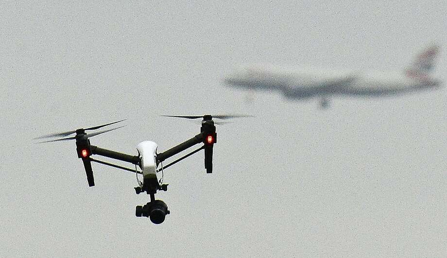 A drone flies in London's Hanworth Park, with a British Airways jet in the background. Photo: John Stillwell, Associated Press