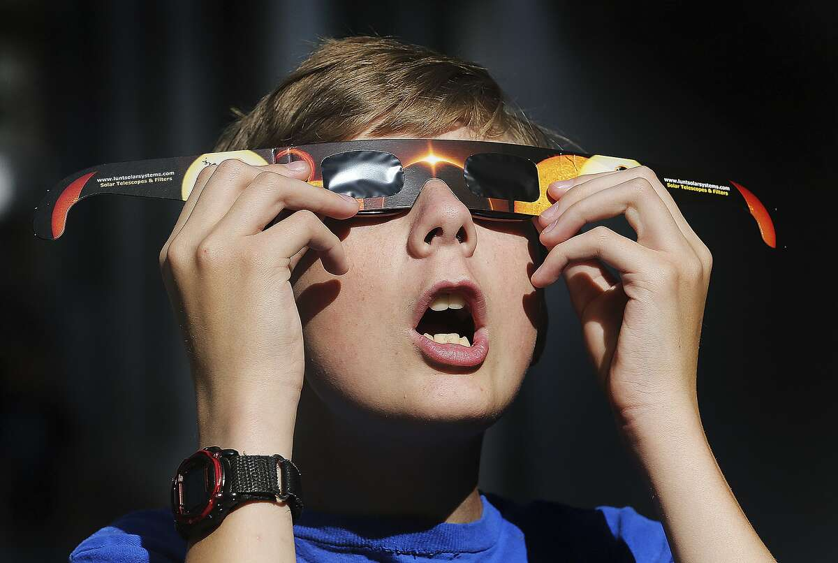 Colton Hammer tries out the new eclipse glasses he bought at the Clark Planetarium in Salt Lake City.