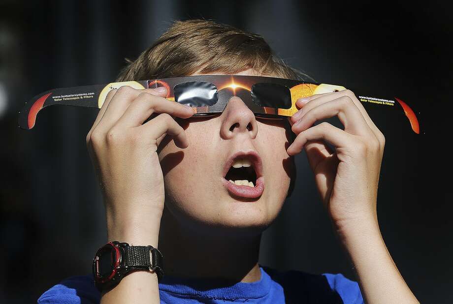 Colton Hammer tries out the new eclipse glasses he bought at the Clark Planetarium in Salt Lake City. Photo: Scott G Winterton, Associated Press